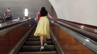 Ut_4614# Under the skirt of a brunette in a long yellow sundress. On the subway escalator, you can f