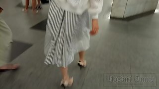 Ut_4229# Upskirt slender brunette in a long white skirt. On the escalator in the subway, you can fin